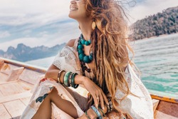 close up of fashionable young model in boho style dress on boat at the lake