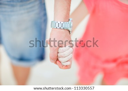 Close up of father and daughter holding hands at beach