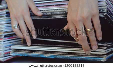 Close Up Of Female Adult Hands Wearing Various Rings Browsing Through Vinyl Records.
