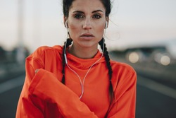 Close up of female athlete relaxing during workout standing outdoors. Fitness woman doing exercises outdoors and listening to music with earphones.