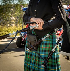 Close up of female bag piper holding bagpipes dressed in a traditional kilt