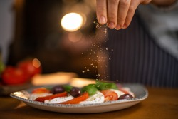 Close up of female chef hands seasoning a plate of freshly made tomato and mozzarella salad.