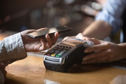 Close up of female client hold smartphone paying for order using modern easy nfc technology, waiter give card reader machine for customer make payment transaction with cashless contactless method