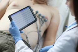 Close-up of female doctor cardiologist check patient results on modern tablet. Protective uniform and gloves. Physician woman diagnostic mans heart. Medicine and ecg concept