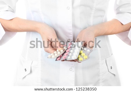 Close-up of female doctor hand holding pills, isolated on white