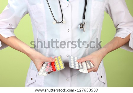Close-up of female doctor hand holding pills, on color background