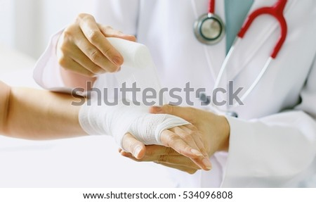 Close-up of female doctor with stethoscope bandaging hand of patient. (Selective Focus)