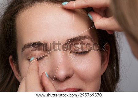 Close-up of female face during eyebrow correction procedure