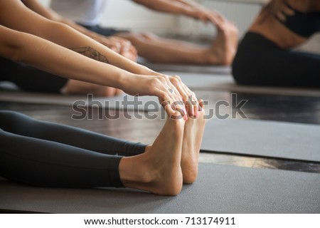 Close up of female feet, group of young sporty people practicing yoga lesson with instructor, sitting in paschimottanasana exercise, Seated forward bend pose, working out, studio, concept