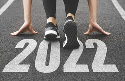close-up of female feet in sneakers at the start. Beginning and start of the new year 2022, goals and plans for the next year