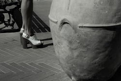 close up of female feet wearing a pair of elegant summer sandals standing aside an iron bench with a big amphora pottery vase in the mediterranean Island of Capri black and white photo