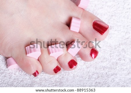 Close-up of female feet with red polished nails carefree