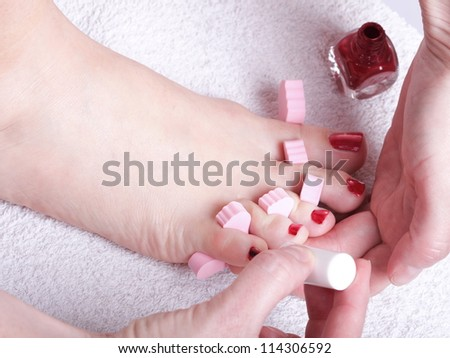 Close-up of female feet with red polished nails carefree, chiropody