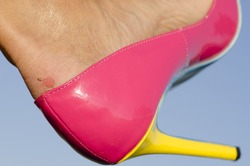Close up of female foot in pink high heel pumps and  painful looking blister on skin, with blue sky as background and copy space.