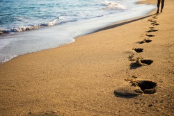 close up of female footprints on the beach