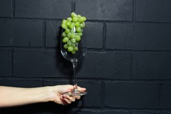 Close-up of female hand holding a wine glass with green grapes inside on background of black brick wall.