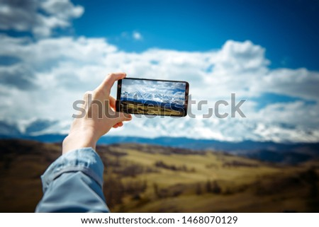 Close-up of female hand holding smartphone and taking photo or video. Woman traveler on the background of a snowy mountain range takes photos on a mobile phone. The concept of travel.