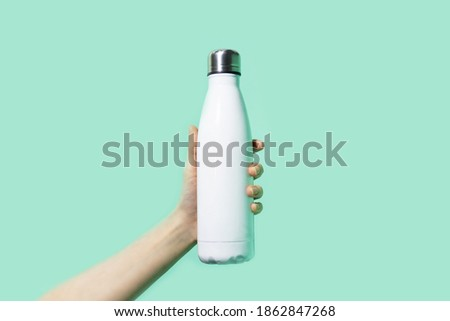 Close-up of female hand, holding white reusable steel stainless eco thermo water bottle on background of cyan, aqua menthe color. Be plastic free. Zero waste. Photo stock ©