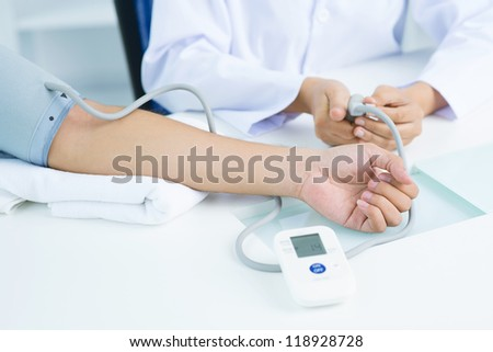 Close-up of female hand in blood pressure gauge