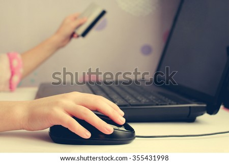 Close up of female hand on computer mouse and holding a credit  card. The concept of online shopping.