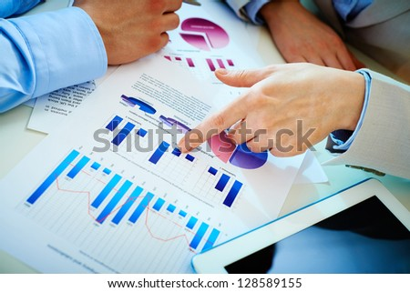 Close-up of female hand pointing at business document in working environment
