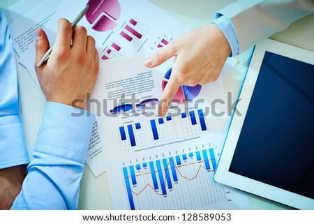 Close-up of female hand pointing at business document while explaining chart