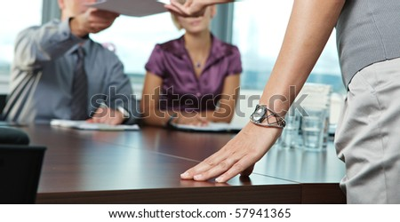 Close up of female hand resting on the table during business meeting. Focus placed on the hand.