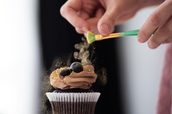 Close up of female hand topping a cupcake. Pastry chef woman making sweet dessert cake. Horizontal image