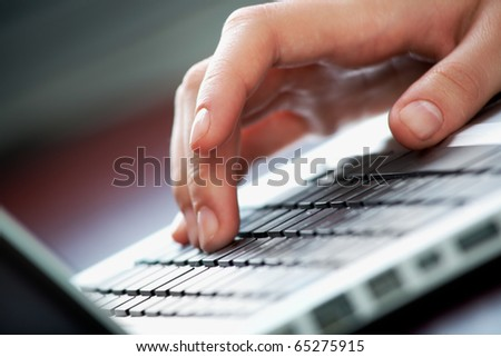 Close-up of female hand touching buttons of keyboard