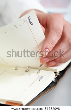 Close-up of female hand turning page of notepad