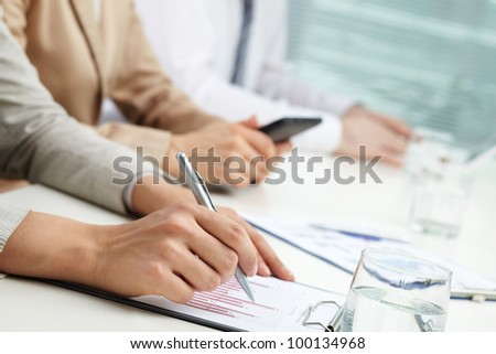 Close-up of female hand with pen over business papers at meeting or lecture