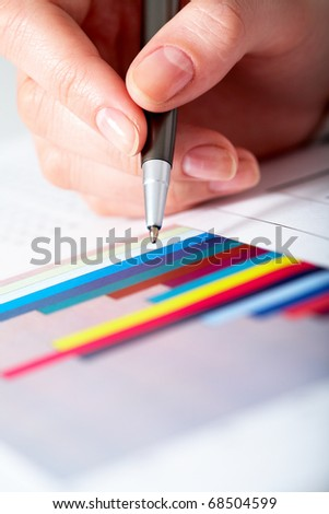 Close-up of female hand with pen over graph