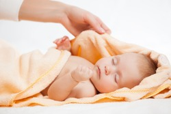 Close up of female hand wrapping sleeping adorable infant in yellow hooded towel. Cute newborn child taking nap after bath. Isolated on white studio background. Concept of baby care.