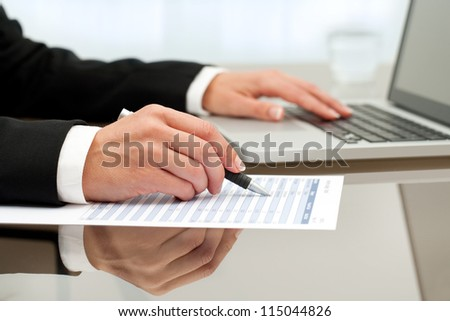 Close up of female hands doing paperwork with pen and laptop.