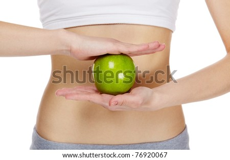Close-up of female hands holding an apple in front of belly