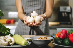 Close up of female hands holding champignon mushrooms in their hands in the kitchen.