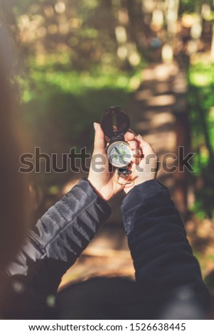 Close up of female hands holding compass against forest footpath. Nature orientation concept. #1526638445