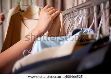Close-up of female hands holding hangers with two blouses taken from the rack with clothes and she choosing one