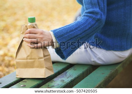 Close up of female hands holding shopping bag with bottle of alcohol drink inside #507420505