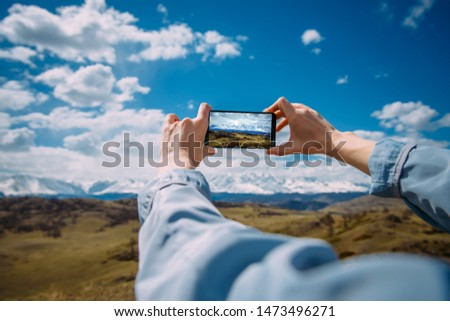 Close-up of female hands holding smartphone and taking photo or video. Woman traveler on a background of beautiful mountain landscape takes photos on a mobile phone. Travel concept.