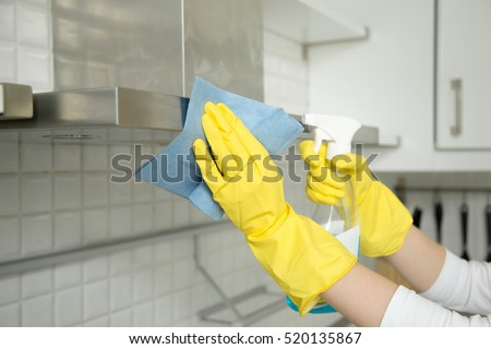 Close up of female hands in rubber protective yellow gloves cleaning the kitchen metal extractor hood with rag and spray bottle detergent. Home, housekeeping concept #520135867