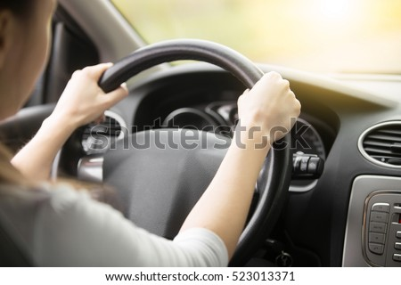 Close up of female hands on the steering. Traveler girl on car trip, looking at the road. View over shoulder  #523013371