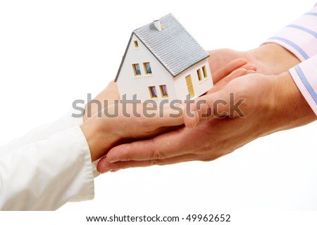 Close-up of female hands passing toy model of house to male