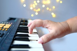 close-up of female hands presses the black, white keys of the electronic piano, plays a melody, musician enjoys music, learning concept, creative self-realizatio