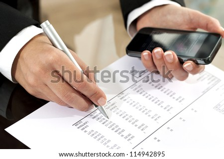 Close up of female hands reviewing accounting documents with smart phone.