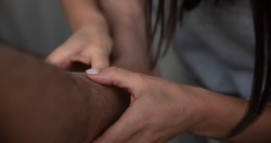 Close up of female hands take out a splinter from a male leg.