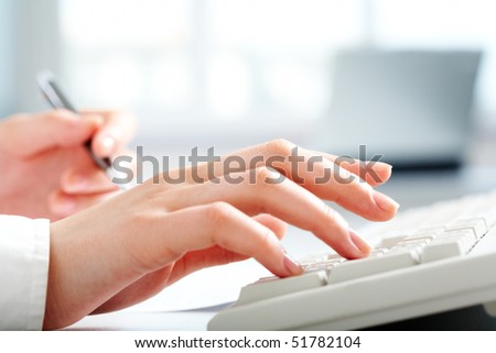 Close-up of female hands touching buttons of white keyboard and holding pen