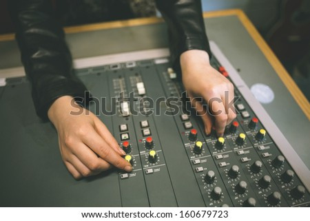 Close up of female hands turning up volume in radio studio at college