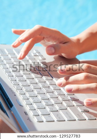 Close-up of female hands typing on a laptop in front of the pool