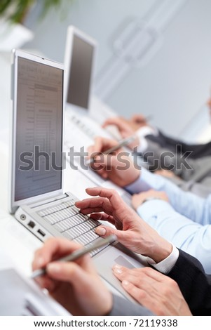 Close-up of female hands typing on computer keyboard in working environment - stock photo